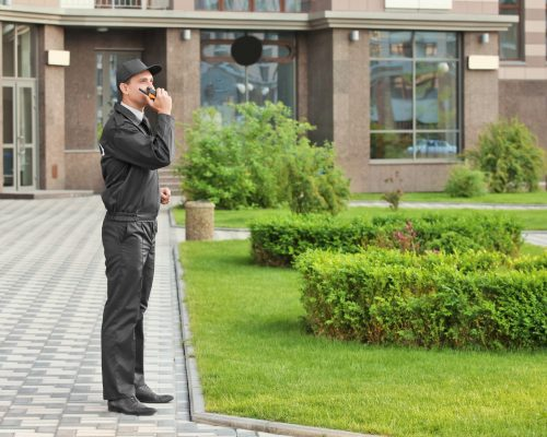 Male security guard with portable radio, outdoors